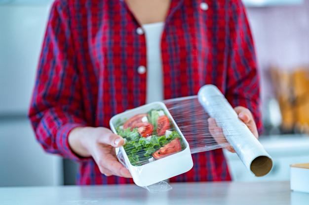 pessoa tampa salada com filme plástico, embalagem