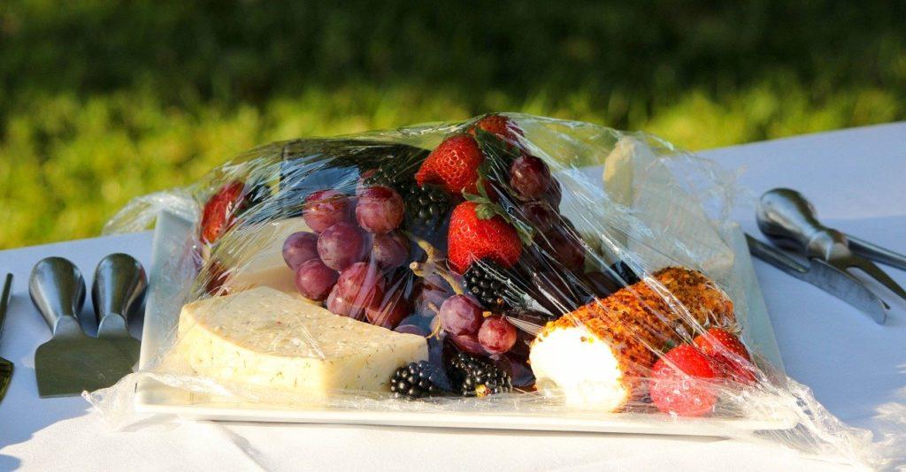 Queijo, frutas e pão embalados com celofane sobre uma tolha em cima da grama