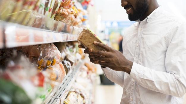 Homem escolhe pão em prateleira de supermercado