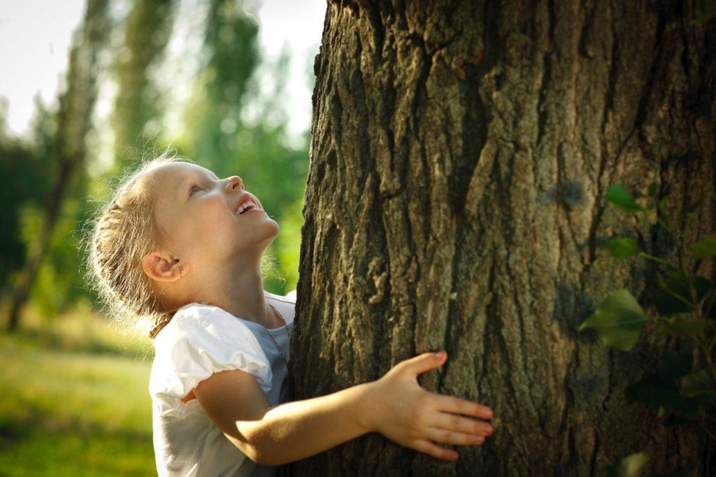 Menina abraça uma árvore. O futuro precisa ser sustentável.